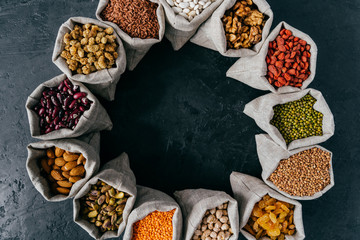 Food and nutrition concept. Horizontal shot of sacks filled with protein rich dried fruits and legumes. Almonds, walnuts, raisins, pink seeds.