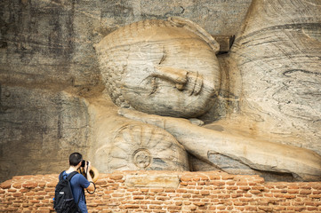 (Selective focus) A tourist is taking photos at the beautiful statue of the Reclining Buddha carved in stone. The Gal Vihara is a rock temple situated in the ancient city of Polonnaruwa, Sri Lanka.