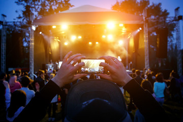 Hands with a smartphone records live music festival