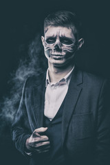 Stylish and beautiful, emotional young man with skeleton makeup in a strict suit against the background of smoke and dark background to Halloween