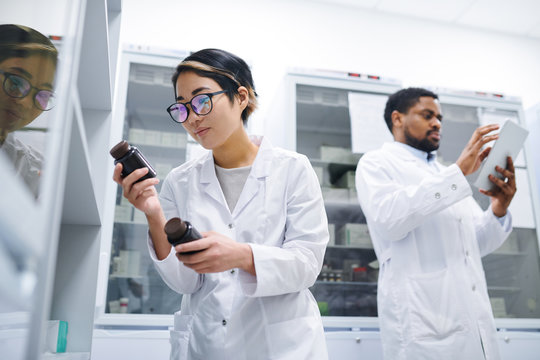 Serious concentrated young Asian female pharmacist with short hair standing at refrigerator with medications and finding necessary pills in medical storage room