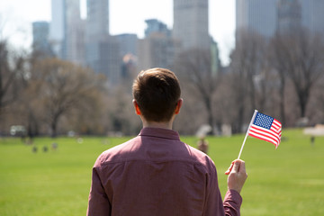 Young man holding American flag and looking at skyscrapers from Central Park, New York City
