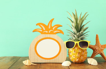 Empty photo frame and funny pineapple with sunglasses. For photography and scrapbook montage