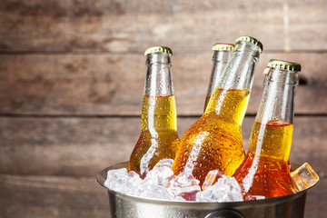 Cold bottles of beer in the bucket on the wooden background