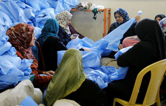Widows and divorced women work at Waladi textile factory, part of which was destroyed by the war in Mosul