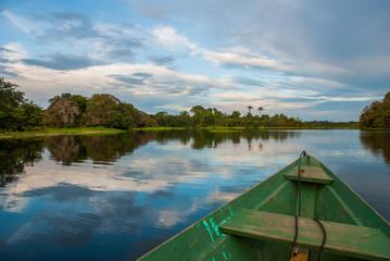 Traditional wooden boat floats on the Amazon river in the jungle. Amazon River Manaus, Amazonas, Brazil.
