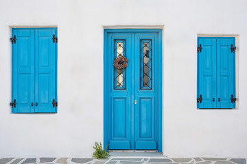 White house facade with traditional blue door on Paros island, Cyclades