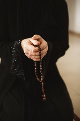 Prayer hands of a woman holding a rosary