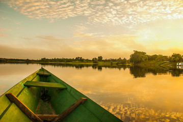 Beautiful sunrise on the river. View from the boat at Amazon river, with a dense forest on the shore and blue sky, Anazonas, Brazil