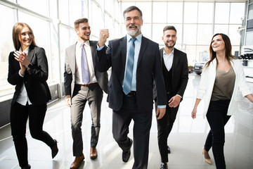 Business People Team Walking In Modern Office, Confident Businessmen And Businesswomen In Suits Diverse With Mature Leader In Foreground.