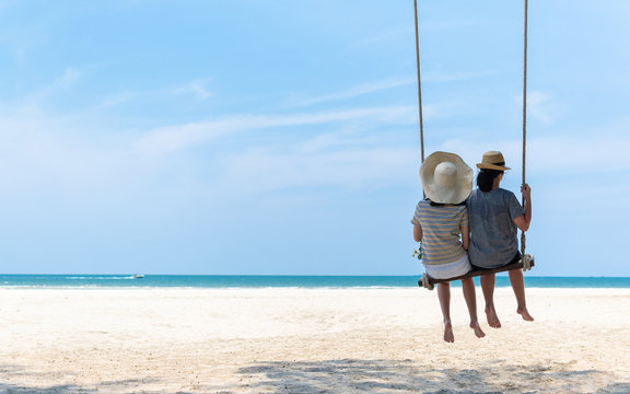 Friendship on summer sandy beach holiday vacation with young couple or teeanger friends relaxing sitting on swing enjoying tropical ocean view, beautiful blue sunny sky on sea shore