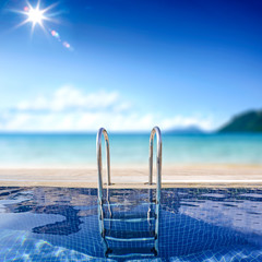 Summer background of swimming pool and free space for your decoration. Beach and sea landscape and blue sky with sun .