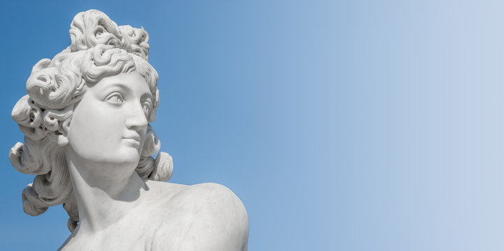 Ancient statue of sensual Italian renaissance era woman with long neck and curly hairs at blue sky gradient background, Potsdam, Germany
