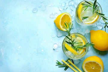 Summer citrus cocktail or lemonade with rosemary. Top view with copy space.