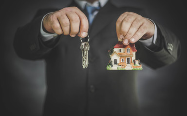 businessman holding house in hand, insurance and mortgage concept