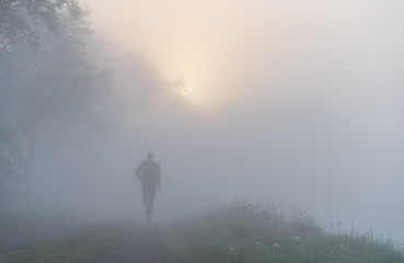 Athlete running on a gravel road during a foggy, spring sunrise in the countryside.