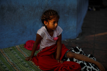 A Nicaraguan migrant girl wakes up after sleeping on the ground as she waits in line to enter the Mexican Comission for Refugee Assistance (COMAR) in Tapachula