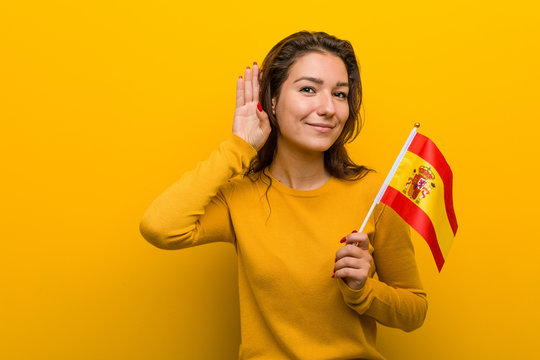 Young european woman holding a spanish flag trying to listening a gossip.