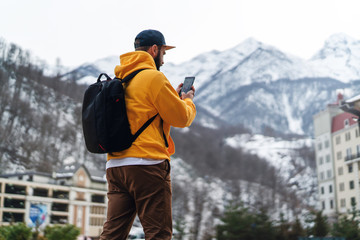 View from back. Man tourist in yellow hoodie, cap with backpack stands on background of high snowy mountains and using smartphone. Wall mural