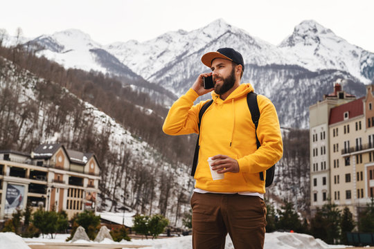Bearded man in yellow hoodie with backpack stands on background of high snowy mountains, talking on mobile phone, drinking coffee.