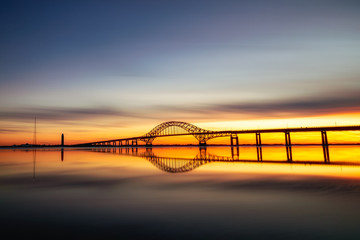Long silhouetted bridge with an arch crossing a crystal clear calm body of water at sunset. Perfect reflections in the water - Long Island New York.