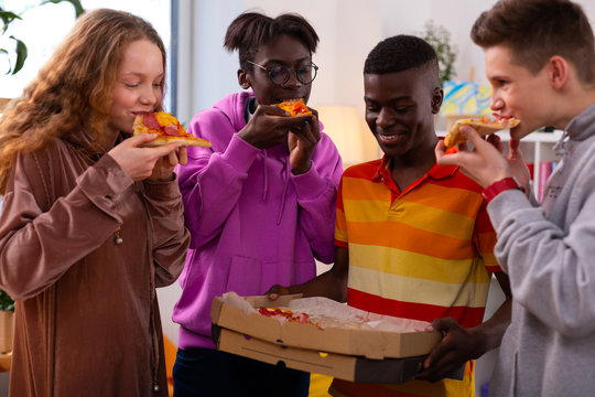 Four stylish teenagers eating delicious pizza after school