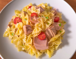 Pasta with tuna and tomatoes in a white plate on a wooden table top view