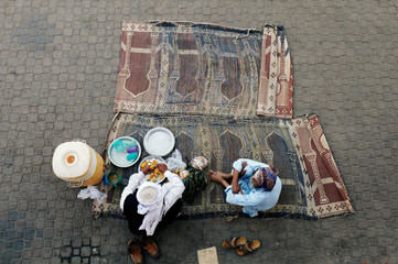 A man chats with other as he is preparing fruit plate for the passengers to break fast, along a railway platform, during the fasting month of Ramadan in Karachi,