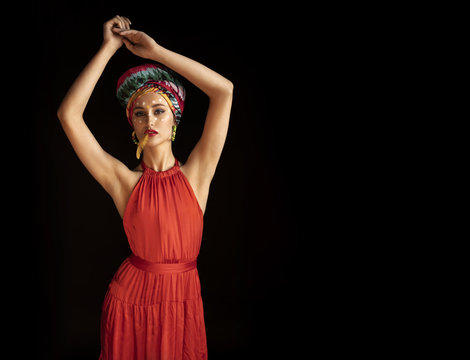 The model poses in the image of an Oriental Princess in a photo Studio on a dark background. model in a bright outfit and red dress. girl with a feather in her lips. free space for copypasters