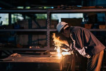 Female welder working in heavy industry factory.