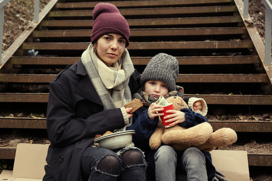 Poor mother and daughter with bread sitting on stairs outdoors