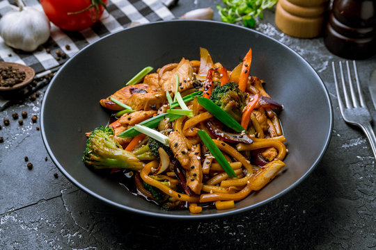 chicken wok noodles on black plate