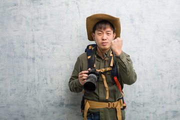 Young chinese explorer man holding a camera showing fist to front, angry expression