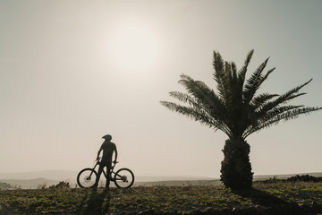 Spain, Lanzarote, mountainbiker on a trip next to palm tree