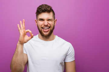 Young handsome caucasian man winks an eye and holds an okay gesture with hand. Wall mural