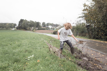 Boy jumping into a muddy puddle