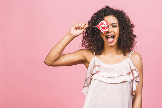 Happy sexy american afro girl eating lollipop. Beauty glamour model woman holding pink sweet colorful lollipop candy, isolated on pink background. Sweets.