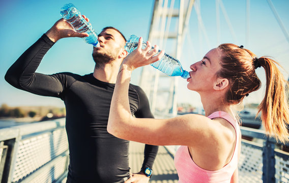 Rest after exercising. Thirsty sportsman and sportswoman drinking water after training outdoors. Fitness, sport, lifestyle concept
