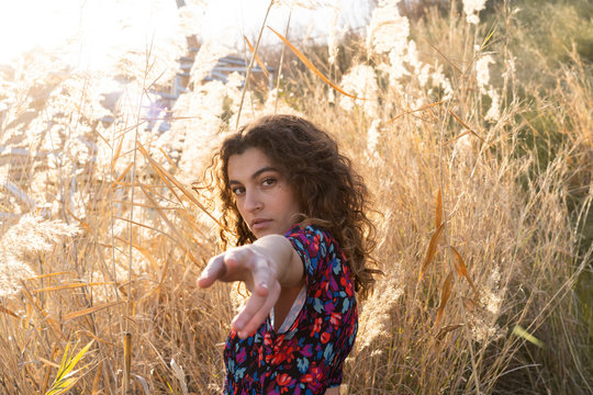 Young woman standing in meadow, reaching out with her hand