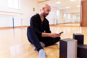 Ballet dancer using cell phone in ballet studio