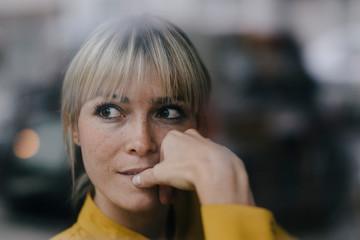 Blond businesswoman sitting at window, thinking