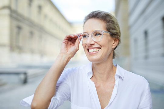 Portrait of smiling woman wearing white shirt and glasses in the city
