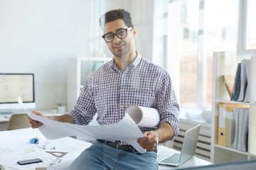 Portrait of young engineer looking at camera while working in office behind glass, copy space