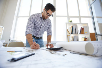 Wide angle portrait of engineer drawing plans and making measurements at workplace, copy space