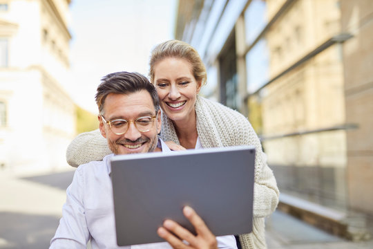 Happy couple using tablet in the city