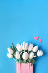 Springtime flat lay, white tulips in paper bag on blue mint background with decorative hearts