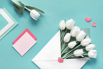 Springtime flat lay, white tulips in paper envelope on green mint background with envelopes, cards and decorative hearts