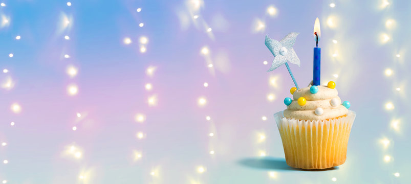 Celebratory cupcake with a decorative lit candle