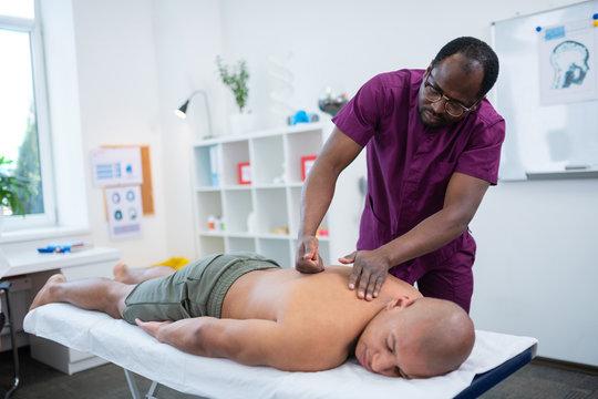 Dark-skinned massage therapist using fists while doing massage