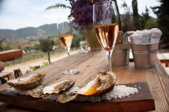 Pair of glasses one with sparkling pink wine and another with red wine placed on wooden table for pairing with oysters cooked in gourmet style